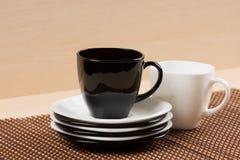 Закройте вверх по взгляду чашки черного чая на стоге белых и черных плит около белой чашки чая на tablemat Стоковое Изображение RF