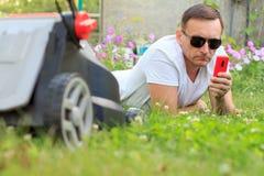 Закройте вверх по взгляду человека лежа на зеленой траве перед косить ее Стоковая Фотография