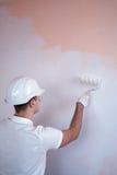 Закройте вверх по взгляду человека держа ролик краски стоковая фотография rf