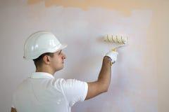 Закройте вверх по взгляду человека держа ролик краски стоковые изображения
