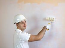 Закройте вверх по взгляду человека держа ролик краски стоковое изображение rf