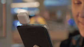 Закройте вверх по взгляду smartphone в руках женщины с специальным донглом для оплачивать карточку акции видеоматериалы