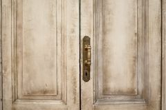Закройте вверх по внешнему взгляду старой деревянной двери гаража Металлические элементы, ручка и keyhole видимы Покрашенные бели Стоковая Фотография