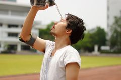Закройте вверх по воде молодого азиатского бегуна лить с waterbottle на его стороне после бежать на следе стоковое фото rf