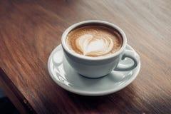 Закройте вверх по горячей кофейной чашке капучино с искусством latte формы сердца дальше Стоковое Изображение RF