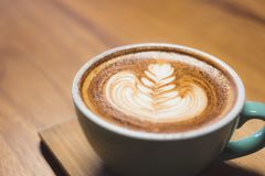 Закройте вверх по горячей кофейной чашке капучино с искусством latte формы сердца дальше Стоковые Изображения RF