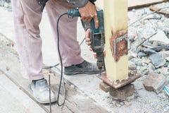 Закройте вверх по детали отверстий работника сверля в стальной конструкции с электрическим сверлильным аппаратом Стоковое Фото