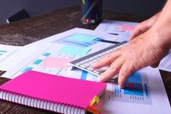 Закройте вверх по деятельности человека архитектора делая эскиз к строительному проекту на его плоском проекте на строительстве м Стоковое фото RF