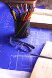 Закройте вверх по деятельности человека архитектора делая эскиз к строительному проекту на его плоском проекте на строительстве м Стоковая Фотография