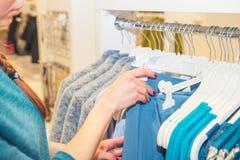 Закройте вверх по женскому ассистенту магазина сортируя через вешалки с одеждами в выставочном зале Сделайте комплект обмундирова стоковые фото