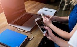 Закройте вверх по женщинам беседуя на телефоне клетки в интернете во время работы на портативном компьютере Стоковое Изображение