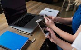 Закройте вверх по женщинам беседуя на телефоне клетки в интернете во время работы на портативном компьютере Стоковая Фотография RF