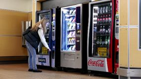 Закройте вверх по женщине покупая бутылку воды на торговом автомате сток-видео