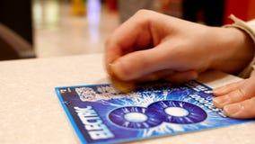 Закройте вверх по женщине царапая вызванный билет лотереи электрическим сток-видео