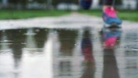 Закройте вверх по замедленному движению снятому ног бегуна в тапках Женские спорт укомплектовывают личным составом jogging outdoo