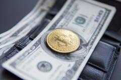 Закройте вверх по золотому bitcoin монетки на нас 100 долларов на коже бумажник с вполне денег Выгода от минировать секретный стоковая фотография