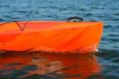 Закройте вверх по изображению красного каяка на красивых реке или озере на вечере Стоковая Фотография