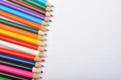 Закройте вверх по изображению много маленьких покрашенных crayons карандаша на белизне Стоковая Фотография