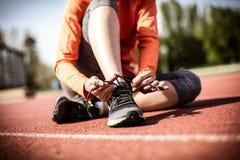 Закройте вверх по изображению молодой женщины спорта связывая ботинки Стоковое Фото