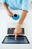 Закройте вверх по изображению рук молодого бизнесмена сидя на таблице указывая на экране компьтер-книжки держа кофейную чашку бел Стоковая Фотография RF