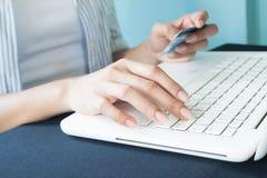 Закройте вверх по изображению рук ` s женщины используя портативный компьютер и smartp Стоковое Фото