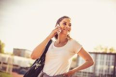 Закройте вверх по изображению телефона молодой женщины спорта говоря Стоковое Изображение