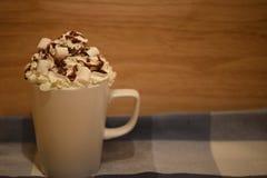 Закройте вверх по изображению фотографии еды питья горячего шоколада в кружке с cream соусом и зефирами на голубой предпосылке тк Стоковое фото RF