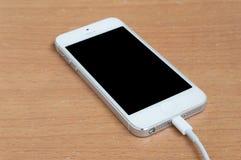 Закройте вверх по кабелю USB на smartphone на столе Стоковое фото RF