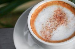 Закройте вверх по капучино кофе на деревянной предпосылке пола Стоковое Изображение RF