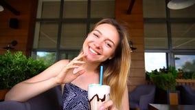 Закройте вверх по коктеилю мороженого и усмехаясь jocund девушке внутри Стоковая Фотография