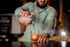 Закройте вверх по коктеилю бармена лить в причудливое стекло стоковые изображения