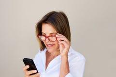 Закройте вверх по коммерсантке при стекла смотря сотовый телефон Стоковые Изображения RF