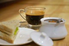 Закройте вверх по кофе americano в чашке и сандвиче на таблице для bre Стоковая Фотография RF
