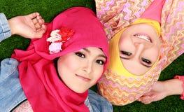Закройте вверх по красивой счастливой мусульманской женщине 2 лежа на траве стоковые изображения