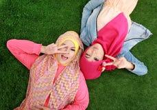 Закройте вверх по красивой счастливой мусульманской женщине 2 лежа на траве Стоковая Фотография RF