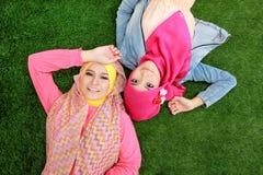 Закройте вверх по красивой счастливой мусульманской женщине 2 лежа на траве Стоковое фото RF