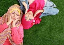 Закройте вверх по красивой счастливой мусульманской женщине 2 лежа на траве Стоковые Фотографии RF