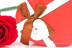 Закройте вверх по красной розе и сформированной сердцем коробке на белизне Стоковые Изображения