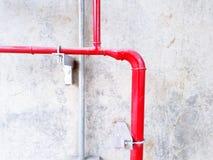 Закройте вверх по красному/серому газу, трубопровод масла и воды установленный на белую бетонную стену с космосом экземпляра стоковые фотографии rf