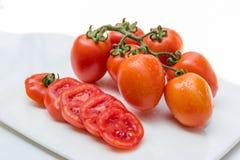 Закройте вверх по красному томату вишни на белой изолированной предпосылке блюда Стоковое Изображение