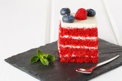 Закройте вверх по красному торту бархата украшенному с голубиками и полениками на белой деревянной предпосылке Стоковое Фото