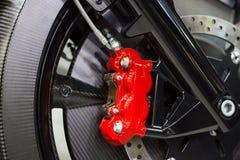 Закройте вверх по красному цвету тарельчатого тормоза мотоцикла новому современному мотоцикла, тормозная система Стоковое Фото
