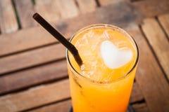 Закройте вверх по кубу льда сердца в апельсиновом соке Стоковое фото RF
