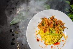 Закройте вверх по лапше Тома yum зажаренной желтой, белым плитам аранжированным на черной предпосылке традиционное еды тайское Стоковое Изображение