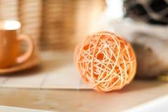 Закройте вверх по лозе шарика ротанга оранжевой на предпосылке деревянного стола с солнечным светом от окна Стоковая Фотография