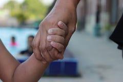 Закройте вверх по матери держа ее руку ` s детей на бассейне, естественном тоне стоковая фотография rf