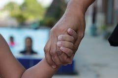 Закройте вверх по матери держа ее руку ` s детей на бассейне, естественном тоне стоковые фото
