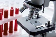 Закройте вверх по микроскопу макроса с пробой крови на белой предпосылке Стоковые Фото