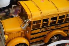 Закройте вверх по миниатюрному школьному автобусу желтого цвета игрушки металла стоковое изображение rf