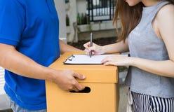 Закройте вверх по молодой женщине кладя подпись в получение доски сзажимом для бумаги d Стоковые Изображения